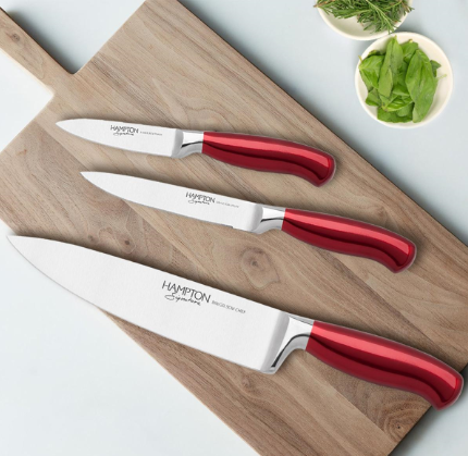 Knives sitting on top of a wooden cutting board
