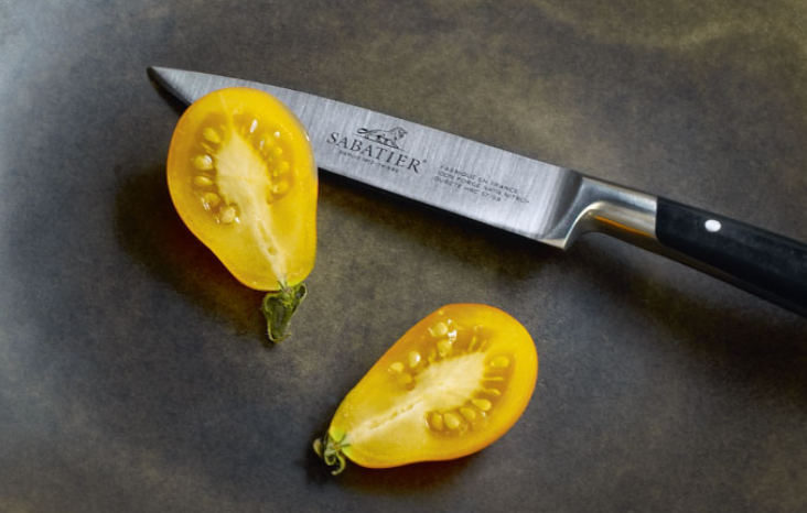 a tomato is cutted by sharp Sabatier knife