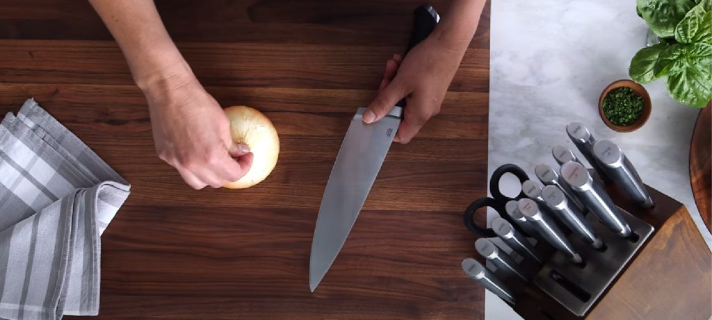 chef using the single Calphalon knife to cut the onion