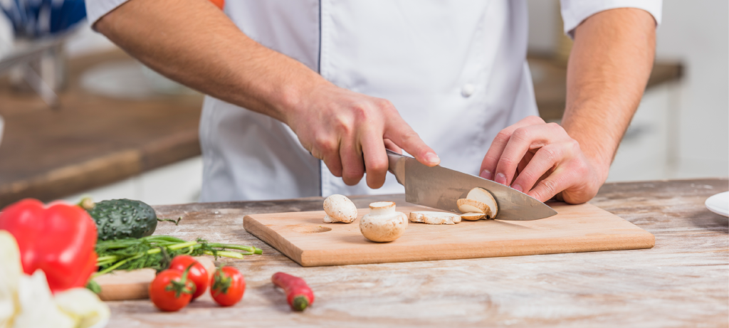 a chef using knife to cut mushrooms