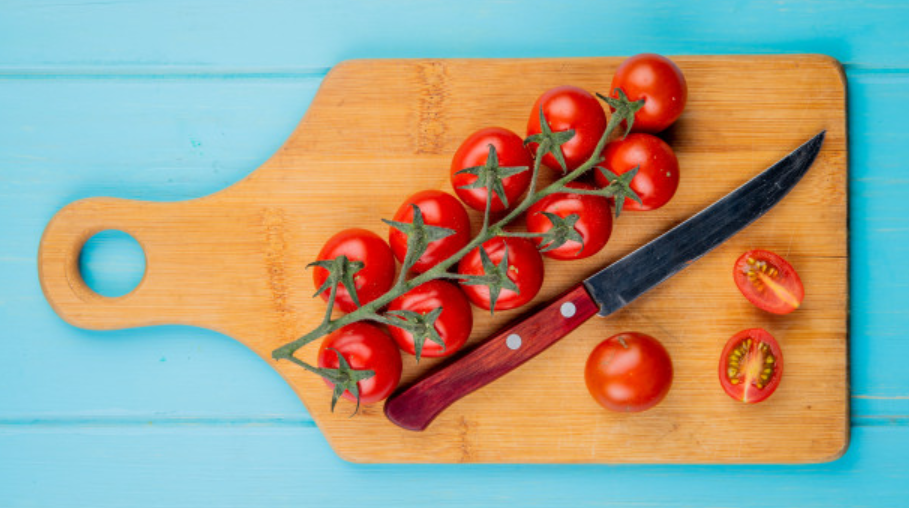 a tomato knife sitting on the board with tomatoes around