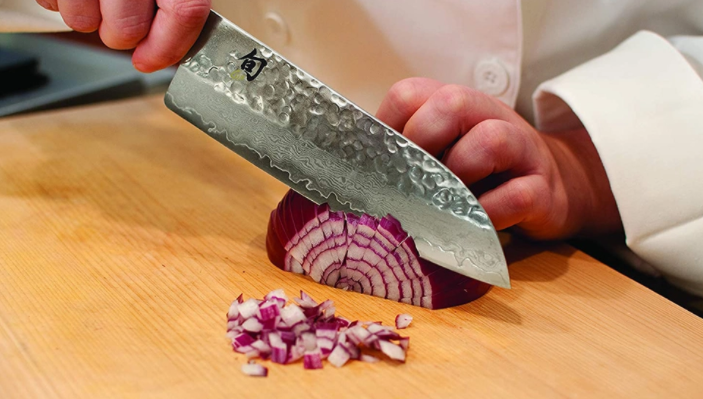 a guy using Santoku knife to cut purple onion