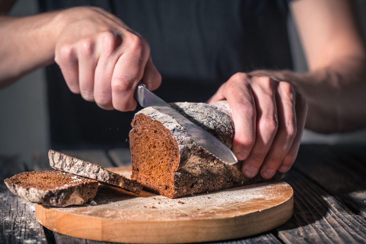 a lady using knife to cut brown bread