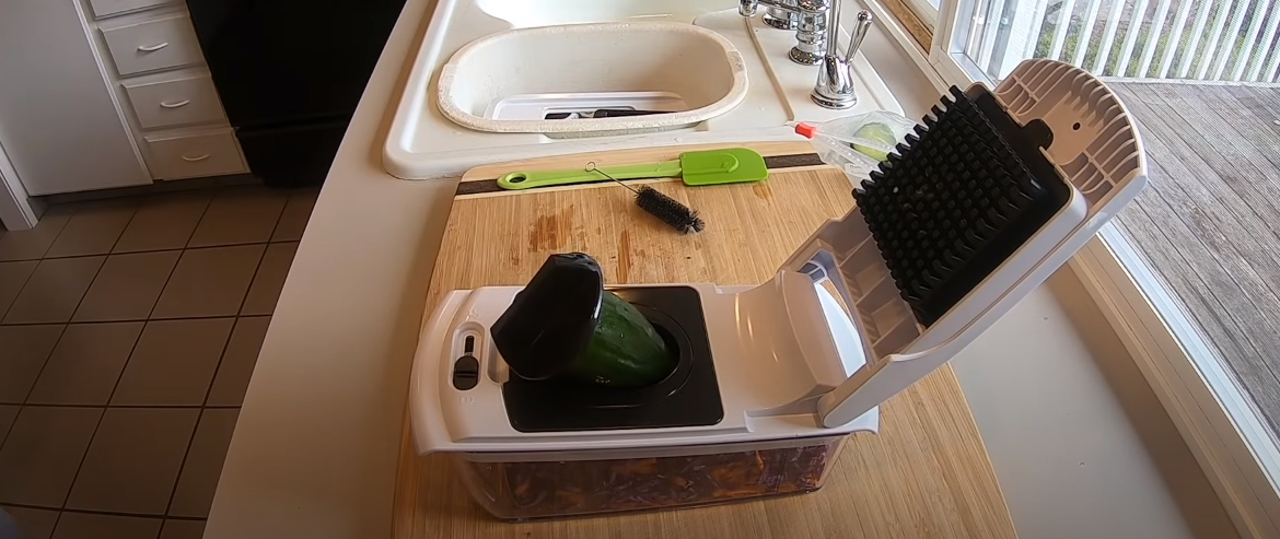 a vegetable chopper sitting next to the sink in the kitchen zone