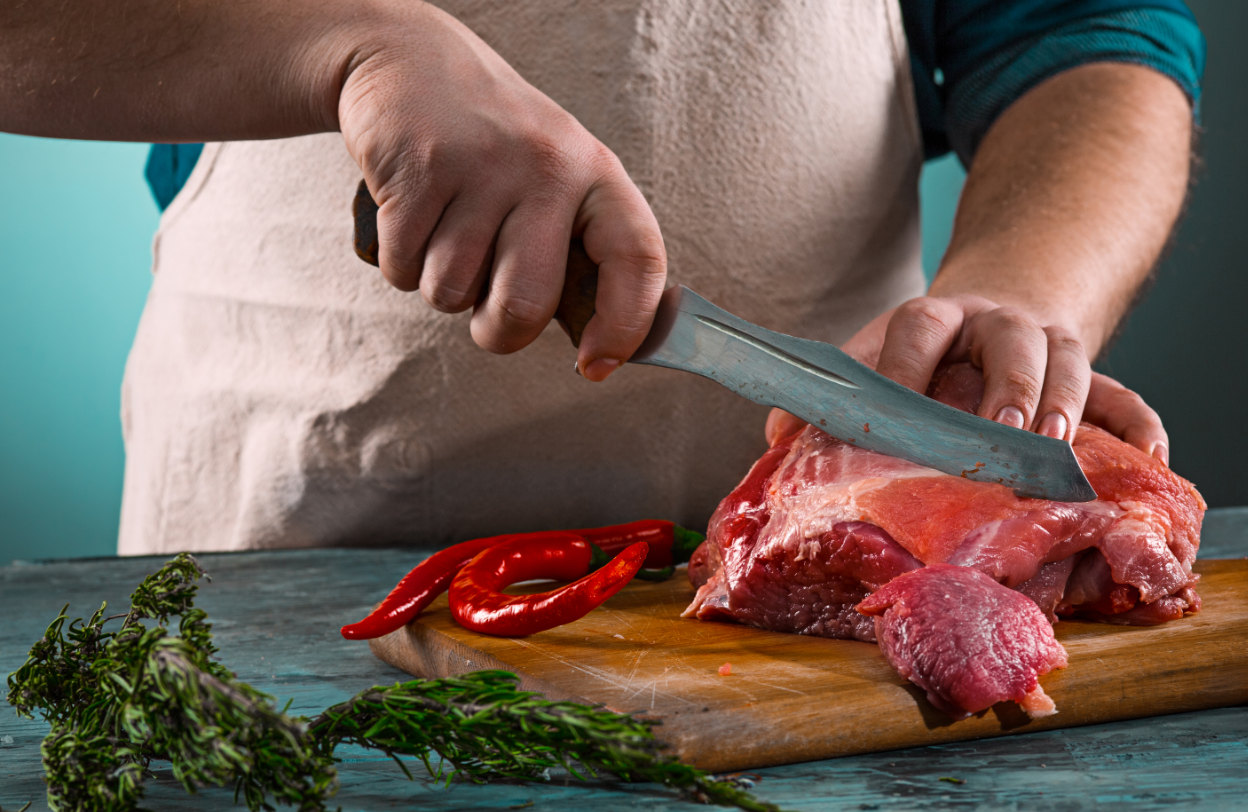 a chef using the butcher knife for meat