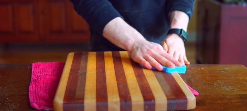 a man is cleaning a cutting board