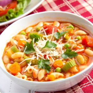 yummy minestrone soup resting in white bowl